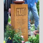 Grabmal aus Holz mit Schrift geschnitzt